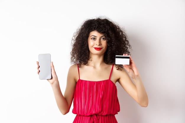 Online einkaufen. modische frau mit lockigem haar, rotes kleid tragend, smartphonebildschirm und plastikkreditkarte zeigend, kamera lächelnd, weißer hintergrund.