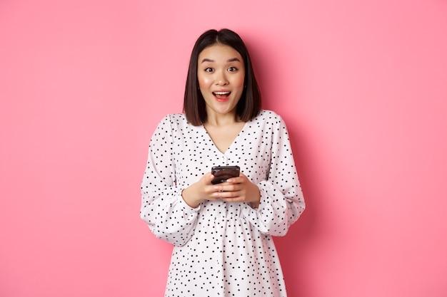 Online einkaufen. überraschte asiatische frau, die mit glücklichem lächeln in die kamera schaut, mit dem smartphone einkauft, die handy-app verwendet und über rosafarbenem hintergrund steht