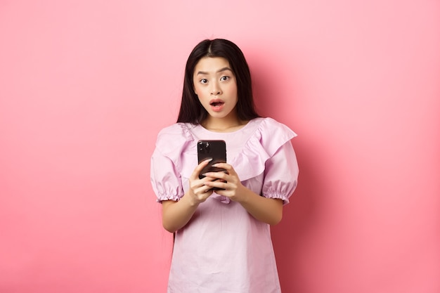 Online einkaufen. überraschte asiatische frau im niedlichen kleid, offener mund erstaunt nach dem lesen der nachrichten auf smartphone, stehend auf rosa hintergrund.