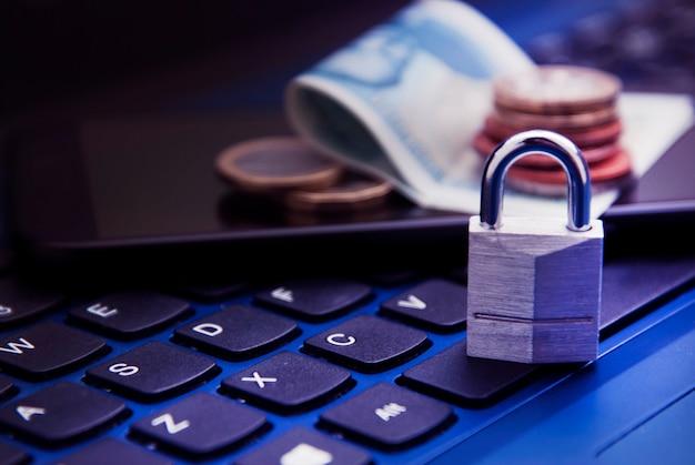 Online einkaufen . vorhängeschloss auf laptop neben geld auf laptop. nicht sicheres online-shopping-konzept.