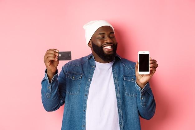 Online einkaufen. zufriedener schwarzer mann nickt zustimmend, lächelt und schaut auf das telefon, zeigt kreditkarte und smartphone-bildschirm und steht über rosafarbenem hintergrund.