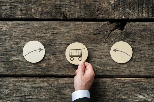 Online-einkaufskonzept - hand eines geschäftsmannes, der drei hölzerne geschnittene kreise mit einkaufswagenikone und pfeilen platziert, die in ihm über hölzernem hintergrund zeigen