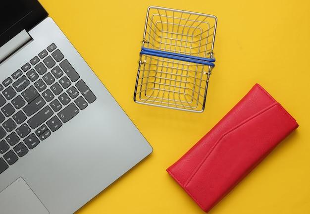 Online-einkaufskonzept laptop-geldbörse und mini-einkaufskorb auf gelbem hintergrund