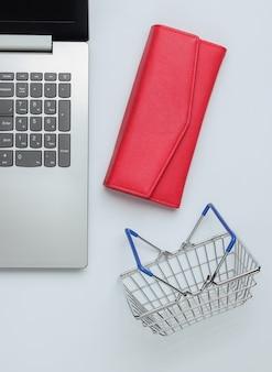 Online-einkaufskonzept laptop-geldbörse und mini-einkaufskorb auf weißem hintergrund