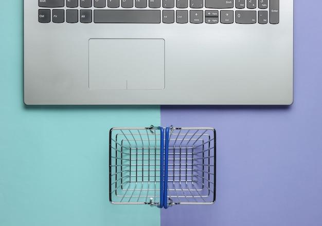 Online-einkaufskonzept laptop und mini-einkaufskorb auf lila-blauem pastellhintergrund