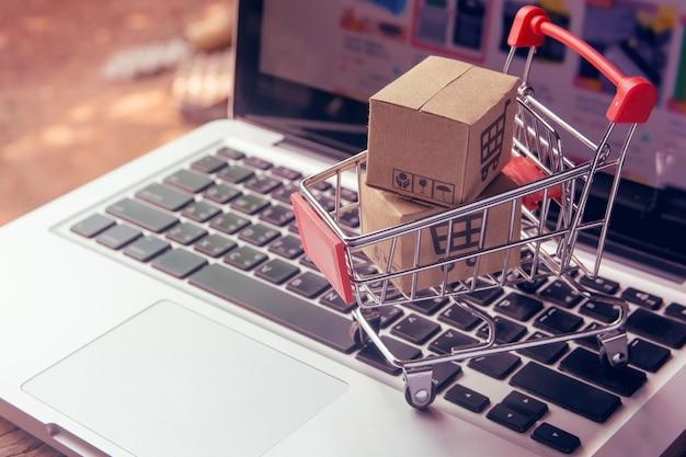 Online-einkaufskonzept - paket- oder papierkartons mit einem einkaufswagenlogo in einem wagen auf einer laptoptastatur. einkaufsservice im online-web. bietet lieferung nach hause.