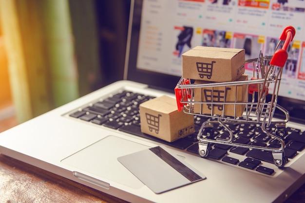 Online-einkaufskonzept - paket- oder papierkartons mit einem einkaufswagenlogo in einem wagen auf einer laptoptastatur.