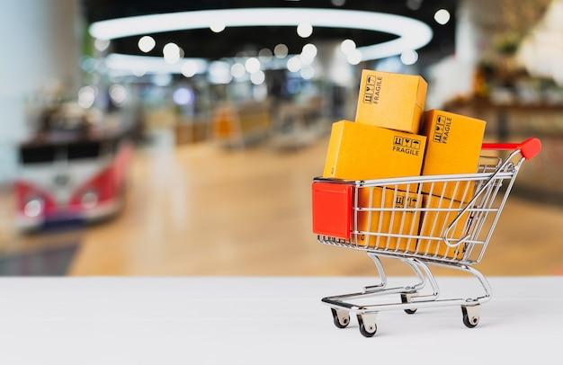 Online-einkaufskonzept, produktpaketbox im warenkorb auf tisch und unscharfer hintergrund des einkaufszentrums