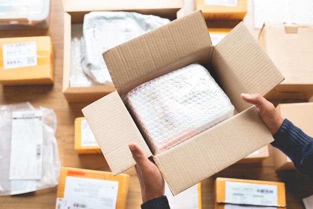 Online-einkaufskonzepte mit männlicher hand, die etwas produkt zu brauner schachtel verpackt