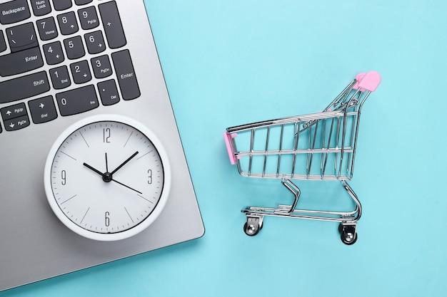 Online-einkaufszeit. computertastatur mit uhr und supermarktwagen auf blauem hintergrund. draufsicht