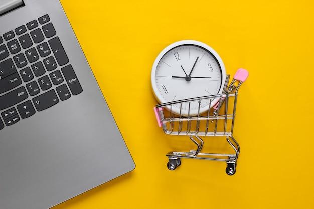 Online-einkaufszeit. computertastatur mit uhr und supermarktwagen auf gelbem hintergrund. draufsicht