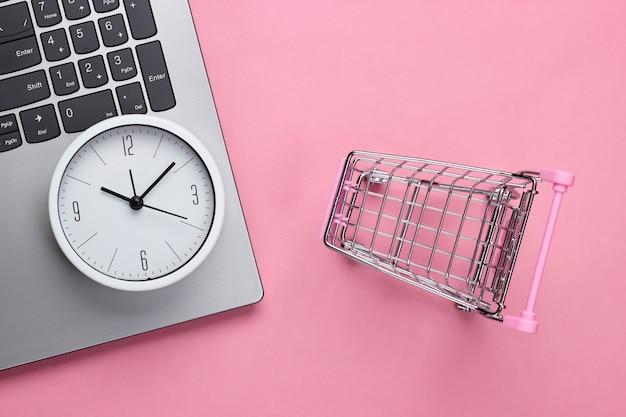 Online-einkaufszeit. computertastatur mit uhr und supermarktwagen auf rosa hintergrund. draufsicht
