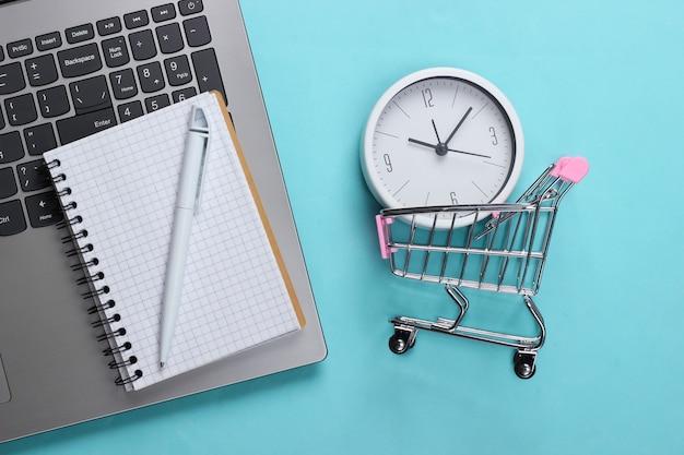 Online-einkaufszeit. computertastatur mit uhr und supermarktwagen, einkaufsliste auf blauer oberfläche. draufsicht