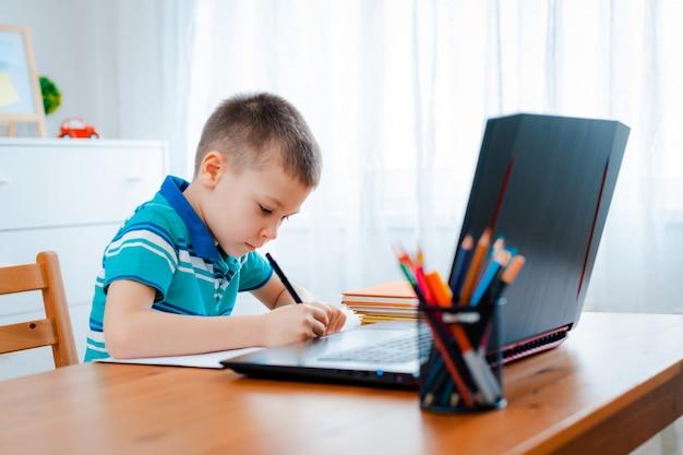Online-fernunterricht. ein schüler lernt zu hause und macht hausaufgaben. ein fernunterricht zu hause