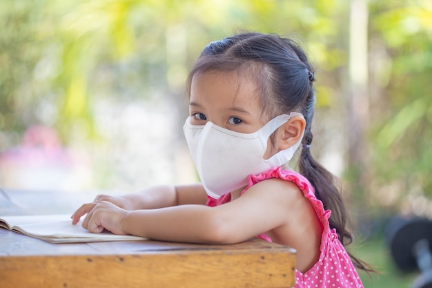 Online-fernunterricht. kind in einer maske, um eine online-lektion zu sehen.