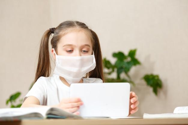 Online-fernunterricht. schulmädchen, das zu hause mit digitalem tablet-laptop-notizbuch studiert und schulhausaufgaben macht.