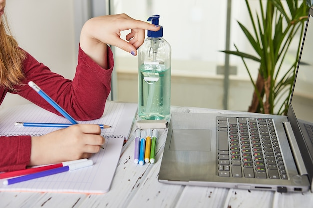 Online-fernunterricht. schulmädchen, das zu hause mit einem laptop lernt und hausaufgaben macht. schulungsbücher und farbige filzstifte auf dem tisch, gel mit alkohol zu 70 prozent