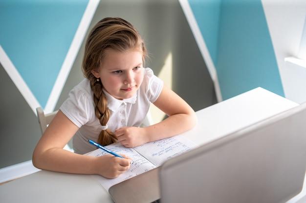 Online-fernunterricht schulmädchen, das zu hause mit notizbuch lernt