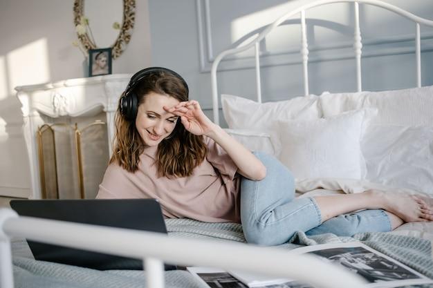 Online-fernunterricht und arbeit. glückliche frau in lässig mit den kopfhörern, die an einem laptop entfernt von zu hause auf dem bett arbeiten.