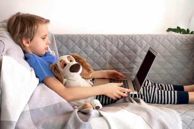 Online-fernunterricht und arbeit. kinder lernen von zu hause aus auf der couch. jungenhände halten laptop