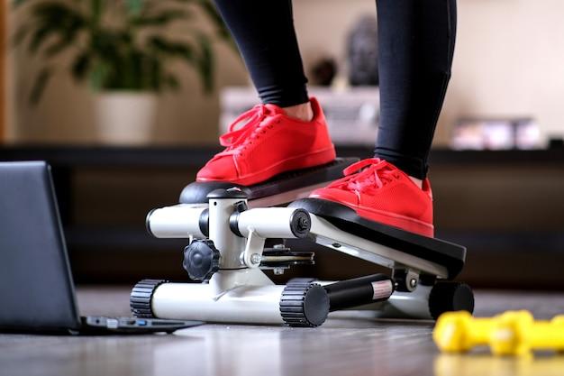 Online-fitnesstraining auf einem stufensimulator. sportliche aktivitäten zu hause während der quarantäne.