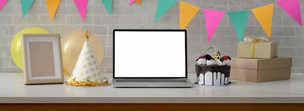 Online-geburtstagsfeier mit leerem bildschirm laptop, kuchen, partyhut und geschenkboxen