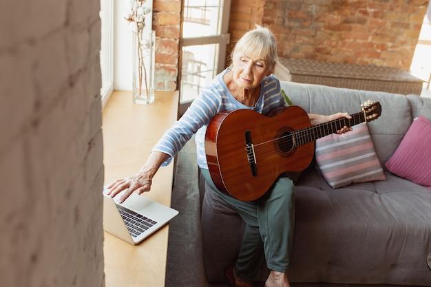 Online gitarre spielen lernen. ältere frau, die zu hause studiert und online-kurse erhält