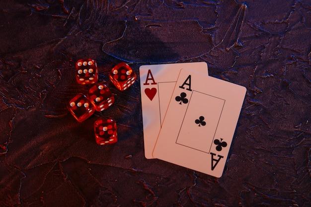 Online-glücksspiel-konzept. asse und fünf rote würfel auf grauem hintergrund