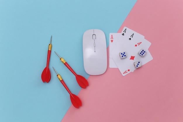 Online glücksspiel. pc-maus, vier asse, würfel, darts auf rosa-blauem hintergrund. ansicht von oben Premium Fotos