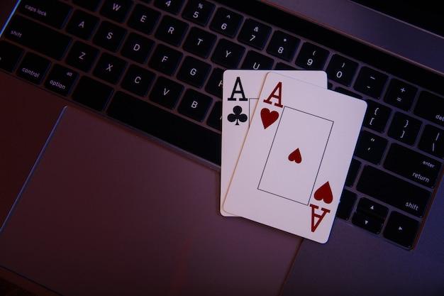 Online-glücksspiel-thema. asse auf der tastatur eines laptops. draufsicht.