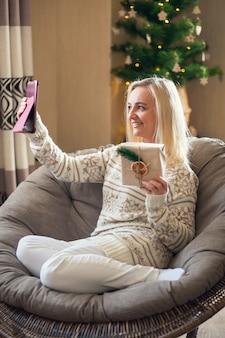 Online-grüße. frau, die eine geschenkbox in der hand hält und ihre lieben online mit tablet begrüßt.