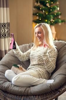 Online-grüße. frau sitzt und grüßt ihre lieben online mit tablet.