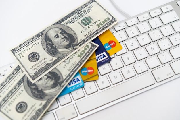 Online-handel, e-commerce, kredit- und debitkarten mit dollar und tastatur.