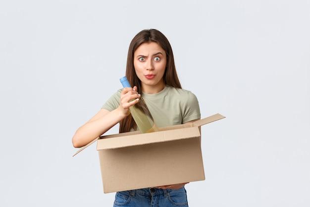 Online-hauszustellung, internetbestellungen und lebensmitteleinkaufskonzept. verwirrte frau offene kiste mit internetbestellung von lebensmitteln, weinflasche zum mitnehmen und verwirrt aussehen, falsche produkte erhalten.