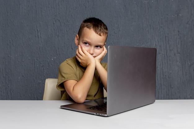 Online-home-learning-konzept. junge, der mit computer sitzt und hausaufgaben macht.
