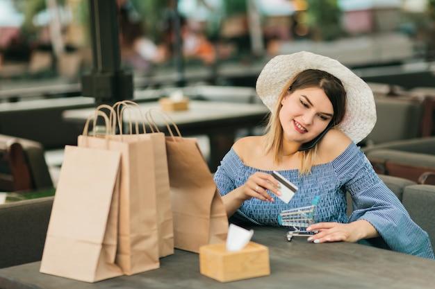 Online junge fröhliche shopaholic frau mit einkaufspapiertüten, die im straßencafé sitzen und kreditkarte und mini-einkaufswagen in ihren händen halten, während am telefon sprechen