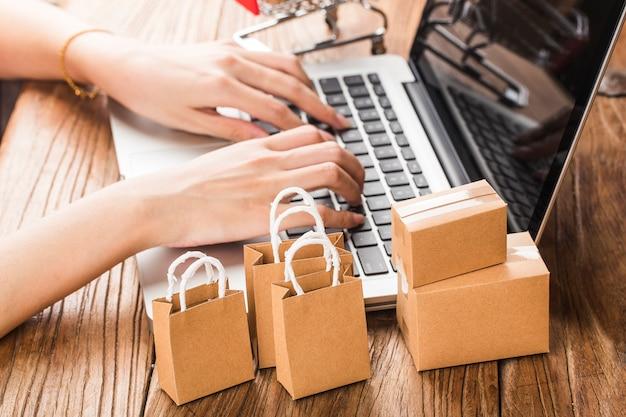 Online kaufen zu hause konzept. kartons in einem einkaufswagen auf einer laptoptastatur.
