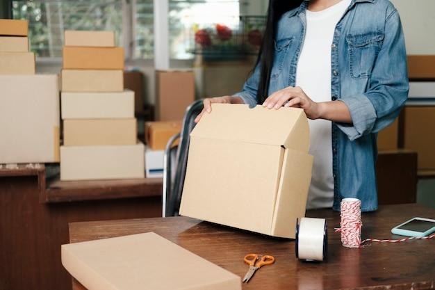 Online-kleinunternehmer. junger startup-unternehmer, online-kleinunternehmer, der zu hause arbeitet, verpackungs- und liefersituation.