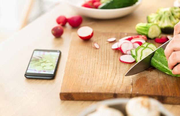 Online kochen oder kochkonzept lernen. mann, der veganes gericht vorbereitet, während rezept im internet unter verwendung des smartphones beobachtet