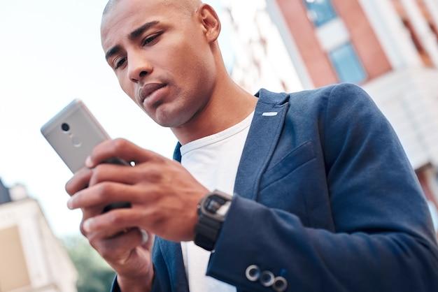 Online-kommunikation junger mann, der auf der straße der stadt steht und smartphone hält, der mit freund chattet