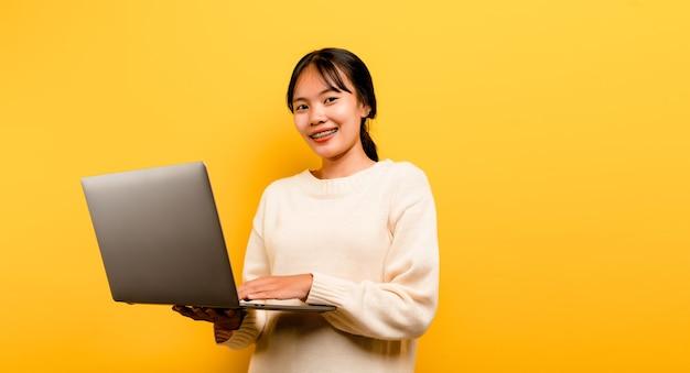 Online-kommunikationskonzept asiatisches mädchen benutzt laptop zu hause gelbes studiofoto sie ist glücklich zu verbringen