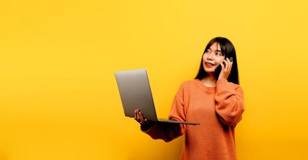 Online-kommunikationskonzept asiatisches mädchen verwendet laptop zu hause gelbes studiofoto sie ist glücklich, ihre freizeit online zu verbringen, während sie mit freunden in sozialen netzwerken chattet, einkaufen oder online arbeitet.