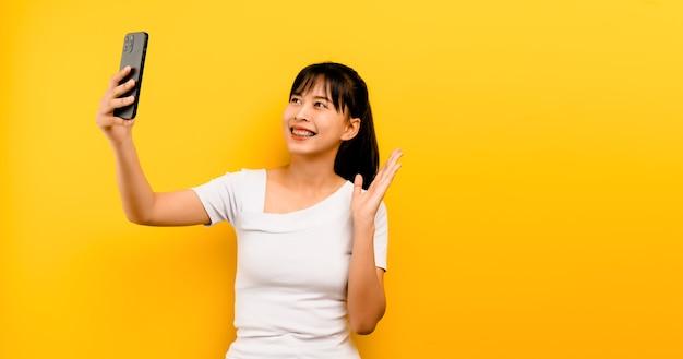 Online-kommunikationskonzept online-lernen des asiatischen mädchenporträts süß glücklich im weißen kleid, das auf dem handy spricht und auf einem gelben hintergrund lacht