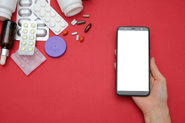 Online-konzept für apotheken und drogerien. medizinpillen und smartphone in den händen auf rotem hintergrund