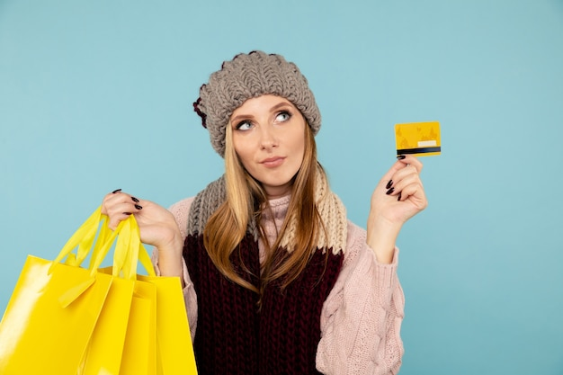 Online-konzept für den wintereinkauf. blonde frau mit kreditkarte isoliert.