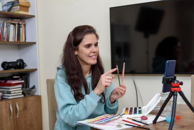 Online-kunstunterricht während der quarantäne. smartphone mit stativ nahaufnahme, lehrer spricht über bürsten in wohnraum verschwommen