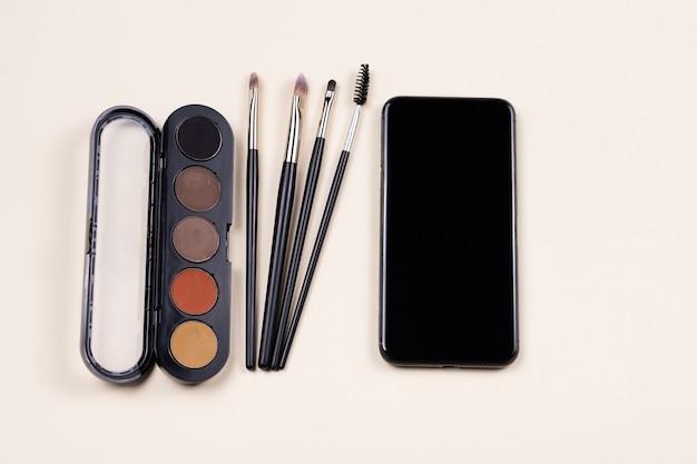 Online-kurs des make-up-studiums. palette von lidschatten, kosmetikpinseln und leerem smartphone-bildschirm