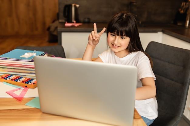 Online lernen. schulmädchen zu hause, online-unterricht, videoanruf auf laptop. fernunterricht, heimschule