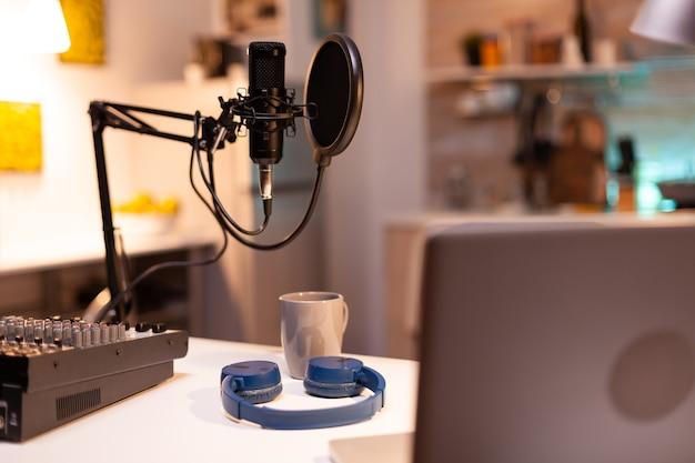 Online-live-podcast-studiotisch mit mikrofon im heimstudio von vlogger. influencer, der social-media-inhalte mit produktionsmikrofon aufzeichnet. digitale web-internet-streaming-station