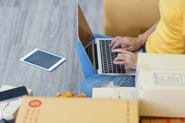 Online-marketing kann einem jungen menschen helfen, ein kleines unternehmen in einem pappkarton zu hause zu gründen.